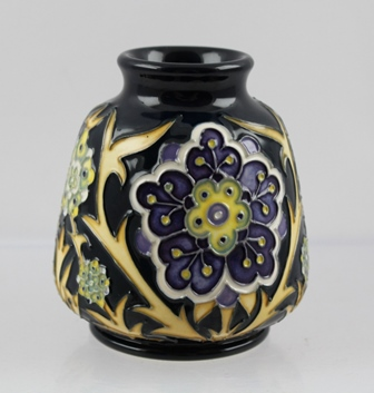 A MOORCROFT CERAMIC VASE, designed by Nicola Slaney, tube lined and hand painted in the Florian Daisy pattern, impressed and painted factory marks to base, 8.5cm high