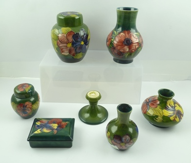 A COLLECTION OF SEVEN PIECES OF GREEN GROUND MOORCROFT CERAMICS, includes a ginger jar and cover with Clematis pattern, a squat vase of Hibiscus pattern, a rectangular box with Flag Iris cover, and other items including a plain green stand or base (7)