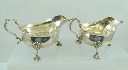 F.C. RICHARDS A PAIR OF GEORGE II STYLE SILVER SAUCE BOATS each with double scrolling handle, raised on triple scallop capped outswept supports on cast scallop feet, Birmingham 1939, combined weight 580g.
