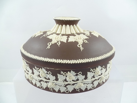 TURNER AN EARLY 19TH CENTURY JASPERWARE OVAL TUREEN AND COVER, chocolate brown ground with applied cameo slip fruiting vine decoration, base impressed Turner, 27cm long, 18.5cm high overall