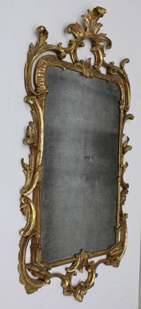 AN 18TH CENTURY CARVED WOOD AND GILDED WALL MIRROR, the frame of Rococo acanthus leaf form, inset early plate - 70cm x 40cm, overall dimensions 115cm x 55cm