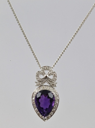 AN AMETHYST AND DIAMOND RHODIUM FINISHED WHITE GOLD COLOURED METAL SET PENDANT, having a central pendeloque cut amethyst bordered by diamonds with a diamond bow above, on a fancy link neck chain, 40cm long, stamped .750, tests 18ct.