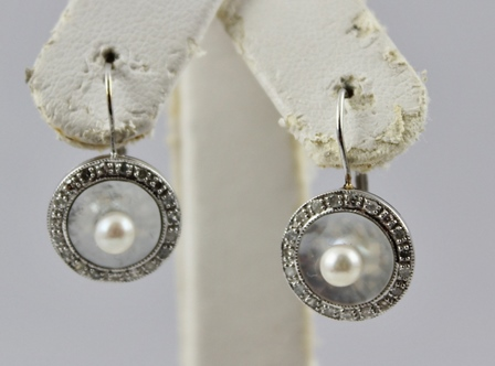 A PAIR OF PEARL AND DIAMOND SET RHODIUM FINISHED WHITE GOLD COLOURED METAL EARRINGS, each having a single cultured pearl set on mother-of-pearl, bordered with diamonds, backed with wire fitting, tests 18ct.