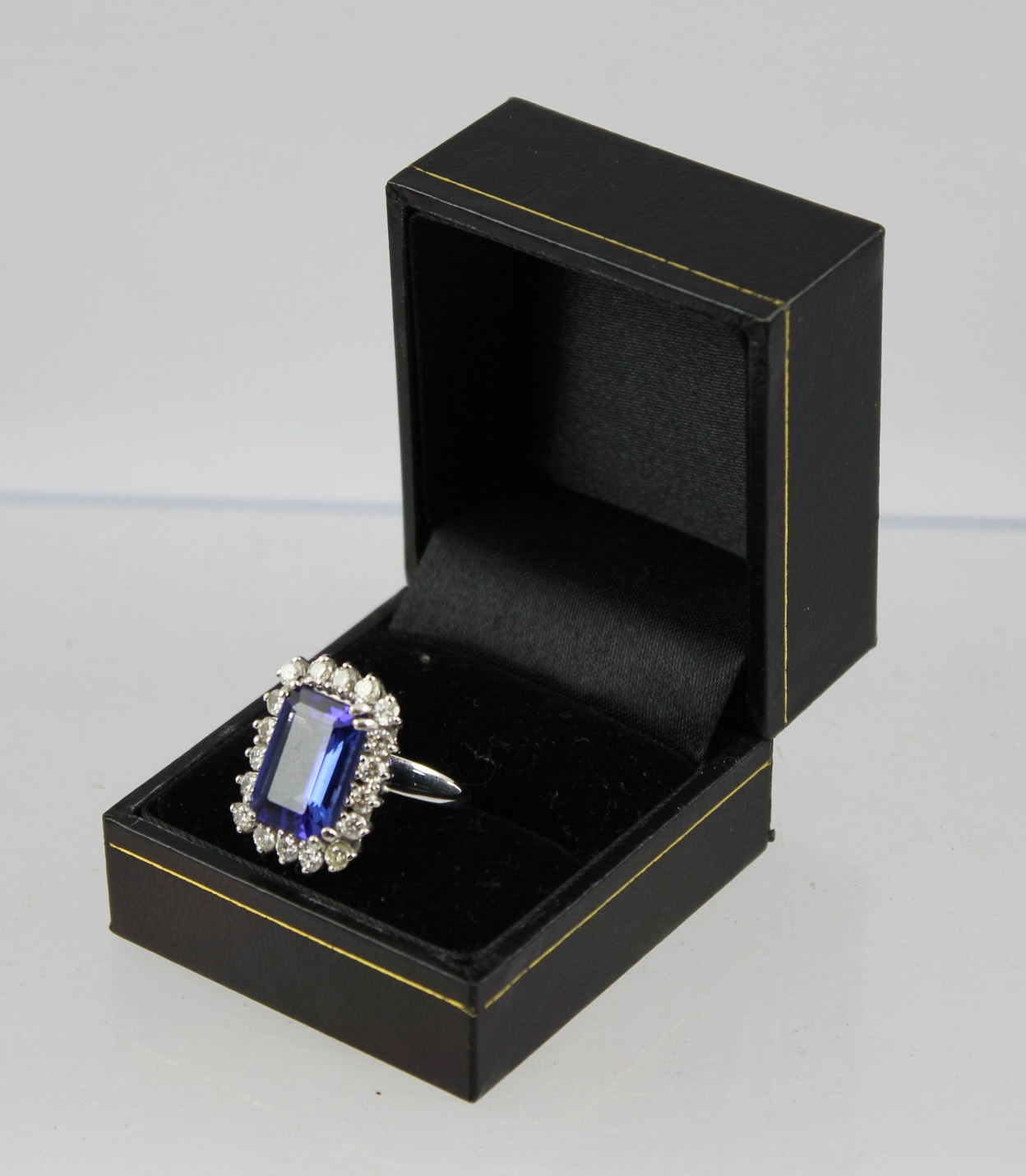 A BLUE TANZANITE & DIAMOND CLUSTER RING, having a trap cut central stone bordered by eighteen brilliants, in rhodium finished white gold coloured metal claw setting, unmarked, setting tests 18ct., centre stone approximately 8cts.)