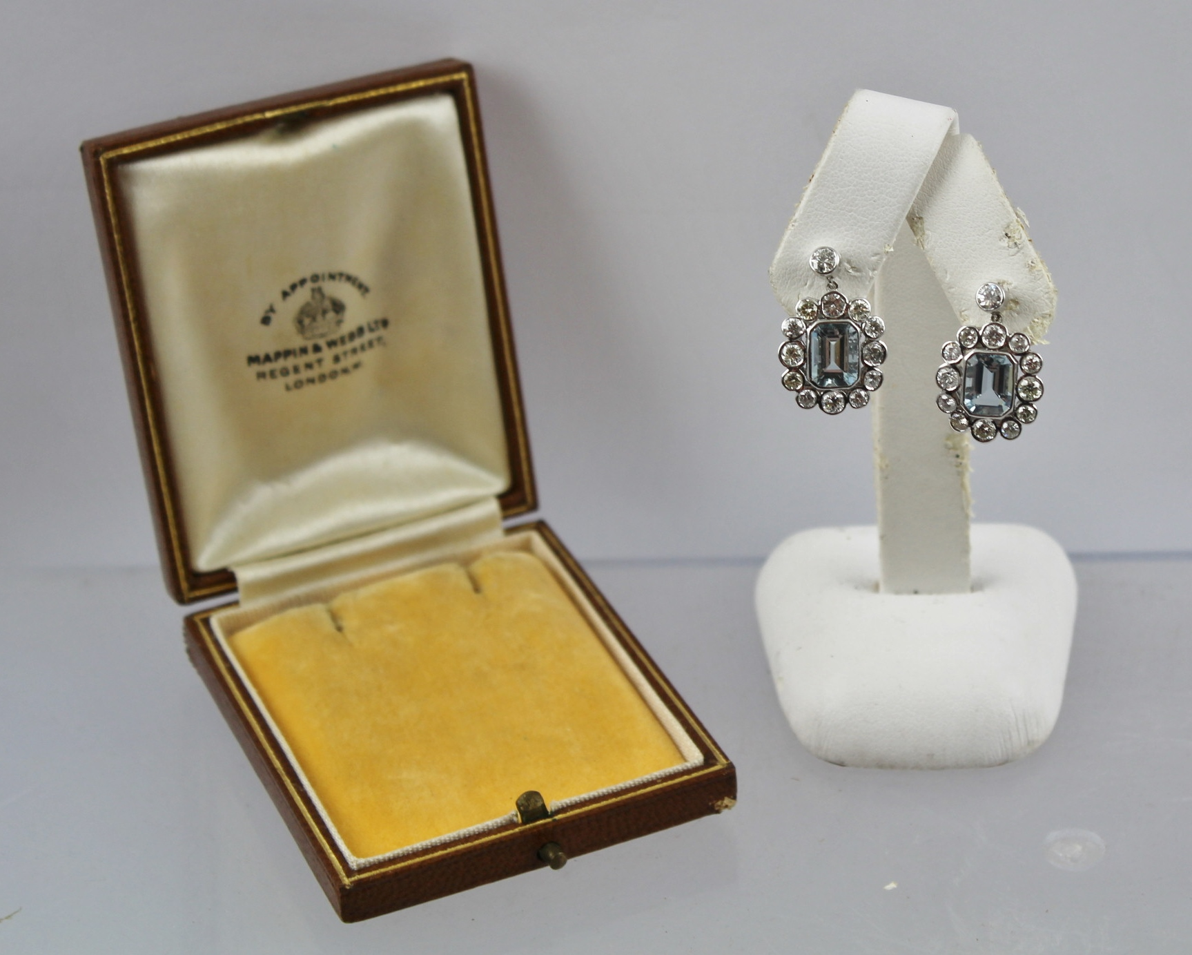 A PAIR OF AQUAMARINE AND DIAMOND CLUSTER WHITE GOLD COLOURED METAL DROP EARRINGS, each having a trap cut rub over set aquamarine bordered by thirteen brilliants, on butterfly drop fittings, in a Mappin & Webb presentation box