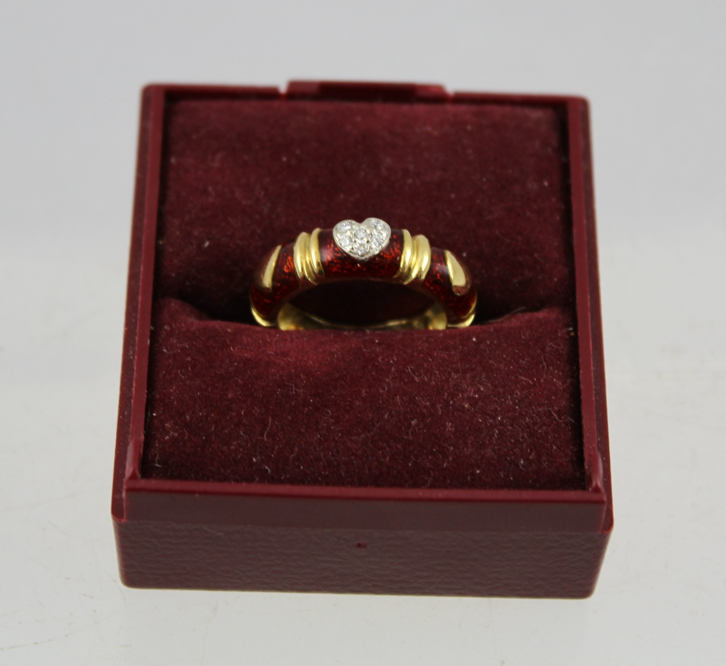 A DIAMOND AND RED ENAMEL MOUNTED FOREIGN GOLD COLOURED METAL ETERNITY RING, the top set with a heart of six small diamonds and flanked by gold hearts in the red enamel, stamped .750 (tested), size K tight