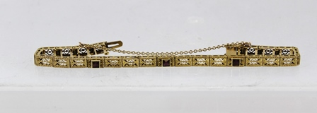 A FOREIGN GOLD COLOURED METAL FLEXIBLE BRACELET comprised of rectangular faceted and wire applied fancy links and three amethysts, stamped 10k