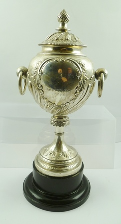 JAMES DEAKIN AND SONS A LATE VICTORIAN SILVER TROPHY CUP of globular form with ring handles, on a tapering stem and platform base, fitted cover with writhen knop, repousse acanthus leaf decoration, engraved cartouche to one side Wallace Kelson Hockey Trophy presented 1945 raised upon an ebonised socle base, Sheffield 1894, the cup and cover stand 34cm high, weight 657g
