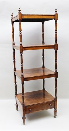 A REGENCY ROSEWOOD FOUR TIER WHATNOT, having turned finials and supports with drawer to base, raised on castors, 130.5cm high x 44cm wide