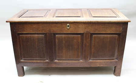 AN EARLY 18TH CENTURY OAK COFFER inset fielded panels, with hinged cover, raised on stile end supports, 117cm wide