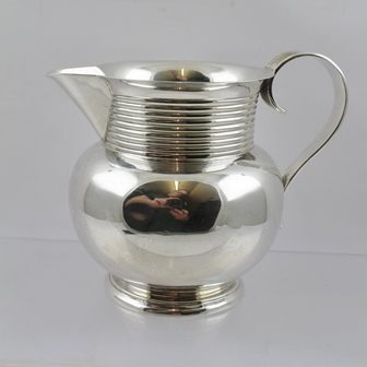 WILLIAM AITKIN A SILVER JUG having ringed neck and reeded flat wire handle, on plain globular body with turned foot, Chester 1900, 337g, 12cm high overall