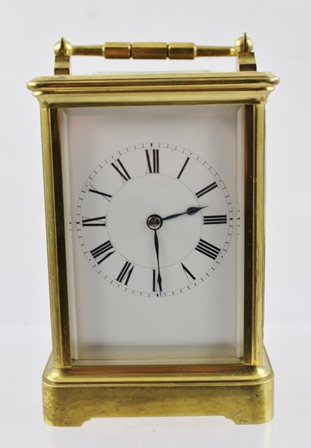 A FRENCH BRASS CASED CARRIAGE CLOCK, hinged handle, bevel plate glass panels, white enamel dial with Roman numerals, the back plate of the 8-day movement, stamped PARIS, 13.5cm high complete with key