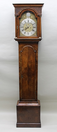 MARK JACOB OF LONDON A WALNUT LONGCASE CLOCK the hood with blind fret panel decoration and brass capped columns flanking an arch topped brass dial with silvered chapter ring, Roman hours and Arabic minutes, with secondary dial and date aperture, having cast decorative spandrels, fitted eight day striking movement, circa 1800, 228cm high