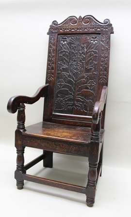 A PART 17TH CENTURY OAK WAINSCOT CHAIR, having high back with scroll crest, over chip carved floral panel, with open scroll arms, plank seat, on ring turned forelegs with plain stretchers