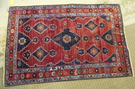 AN AFSHAR HAND-WOVEN WOOLLEN FLOOR RUG, having geometric patterned central field flanked by slender guard borders, the central having stylised flowerhead running pattern, 195cm x 135cm