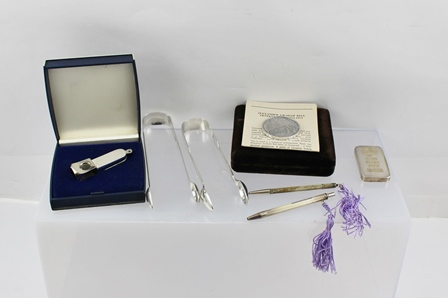 A MIXED LOT OF SILVER COLLECTABLES to include; a 100g ingot paperweight, an engine turned decorated cigar lighter, a commemorative medal - Centenary of Alexander Graham Bell and two pairs of sugar tongs and two dance card pencils, mixed assays