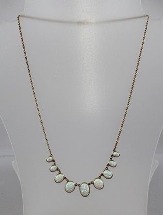 A 20TH CENTURY GOLD COLOURED METAL OPAL NECKLET, having nine oval cabochon stones, each in rub over setting, with belcher style chain and dog clip clasp, tests 9ct, 52cm overall