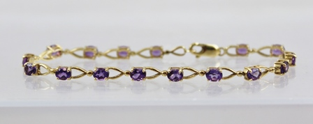 A GOLD COLOURED METAL BRACELET set sixteen oval amethysts in claw mounts