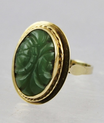 A FOREIGN GOLD COLOURED METAL DRESS RING set oval cabochon carved decorated jade in a rub over surround with wire shank, tests 14k, size P
