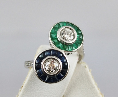A DIAMOND, SAPPHIRE & EMERALD CROSSOVER RING having two central brilliants with a surround of calibre cut emeralds and sapphires, in rhodium finished white gold coloured metal setting with diamond shoulders, un-marked shank, size N tight