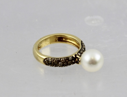 A GOLD COLOURED METAL DRESS RING set multiple cinnamon coloured diamonds and a dangling cultured pearl, size N, tests 18ct gold
