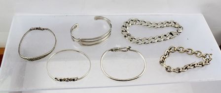 AN ASSORTMENT OF FIVE SILVER COLOURED METAL AND SILVER BRACELETS AND BANGLES comprising; a heavy hammered curb bracelet and a bangle with blue stone, gross weight 162g