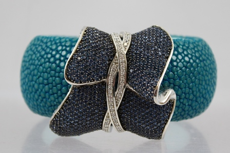A DESIGNER SILVER COLOURED METAL, BLUE CRYSTAL AND RAY SKIN BANGLE, having bi-colour entwined wrap head on turquoise stained base
