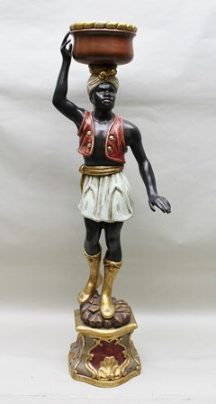 A LATE 20TH CENTURY BLACKAMOOR in the form of a man supporting a bowl/platter on his head, of wooden construction with gesso painted polychrome and gilded decoration, standing upon a decorative plinth base, 158cm high