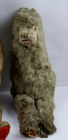 AN EARLY 20TH CENTURY MOHAIR TEDDY BEAR, 50cm high together with an EARLY WAX HEAD DOLL in early costume, 39cm and a photograph c.1914 of the children believed to have owned the toys, also a rabbit fur Yetti, 40cm high