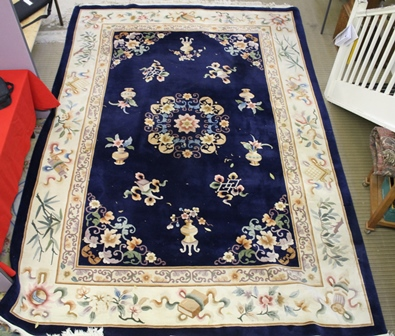 A CHINESE EUROPEAN QUALITY WOOL FLOOR CARPET, having floral central medallion with various precious objects, on deep blue ground, having floral guard border and larger precious objects guard border, with tasselled fringes, 307cm x 436cm