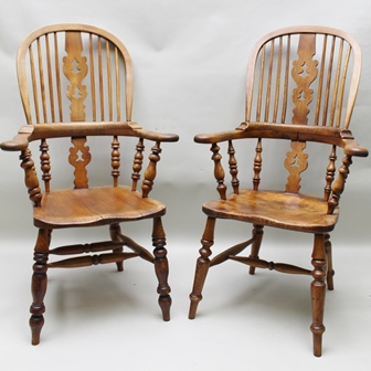 A HARLEQUIN PAIR OF PART 19TH CENTURY CAPTAINS BOW ARMCHAIRS, with associated comb upper section, having shaped pierced central slat, each having turned supports over well-figured solid seat, on splayed legs united by H-shaped stretcher, 117cm highto back crest
