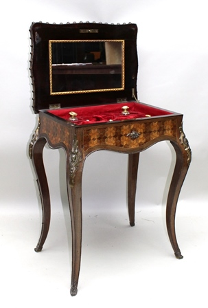 A CONTINENTAL INLAID VANITY FITTED BOX TOP TABLE, having profuse marquetry and applied cast gilt brass decoration, the hinged lid opening to reveal mirror plate and red velvet plush fitted interior with gilded scent bottles and accoutrements, supported on four cabriole legs with metal sabot feet, 71cm x 56cm closed