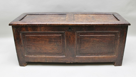 A LATE 17TH CENTURY OAK COFFER having twin panelled lid over a box base, raised on stile end supports, 116cm wide