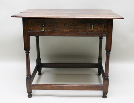 AN 18TH CENTURY OAK PLANK TOP SIDE TABLE, fitted single drawer with brass handles, on turned column supports with plain stretchers, 84cm wide