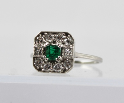 AN ART DECO STYLE 18CT WHITE GOLD EMERAL AND DIAMOND CLUSTER RING, having central square emerald surrounded by diamonds, stamped 18ct, on plain shank, size O easy