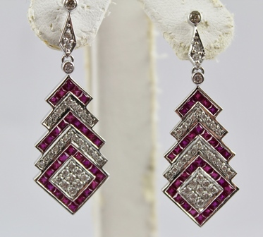 A PAIR OF ART DECO STYLE RHODIUM FINISHED WHITE GOLD COLOURED METAL RUBY AND DIAMOND DROP EARRINGS, each having tiers of diamonds and rubies in geometric style drop, having butterfly fitting