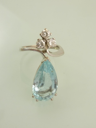 AN AQUAMARINE AND DIAMOND RHODIUM FINISHED WHITE GOLD COLOURED METAL DRESS RING with triple brilliant head over a large aquamarine tear drop, in a modernist claw setting, unmarked, size P
