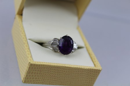 AN AMETHYST AND DIAMOND CLUSTER RING having central oval step cut amethyst, approx 3.95ct with nine baguette cut diamonds to the shoulders, 18ct white gold set