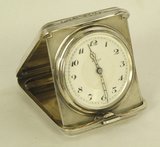 A CONTINENTAL SILVER COLOURED METAL TRAVELLER'S BEDSIDE TIMEPIECE having engine turned exterior, 8-day Swiss 15 jewel mechanism faced with Arabic dial, stamped Sterling Silver