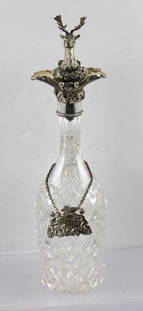 G.R. COLLIS & CO. A SILVER MOUNTED CUT GLASS DECANTER, having hallmarked double pouring spout with vine decoration, the neck of the decanter engraved with fruiting vine, Birmingham 1846, fitted with a cast metal Stags head STOPPER and a BRANDY LABEL on chain