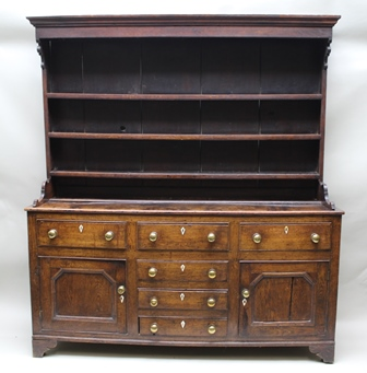 A 19TH CENTURY OAK DRESSER, the base fitted with three drawers over a central bank of three smaller drawers, flanked by two cupboards, brass knob handles, ivory escutcheons, with shelf rack back, raised on bracket feet, 181cm wide x 200cm high