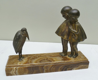 AN ART DECO BRONZED SPELTER FIGURE GROUP depicting two girls fascinated by a Marabou Stork, raised on a brown veined marble plinth, signed in script Demetre Haralamb Chiparus, 37cm wide x 9.5cm high