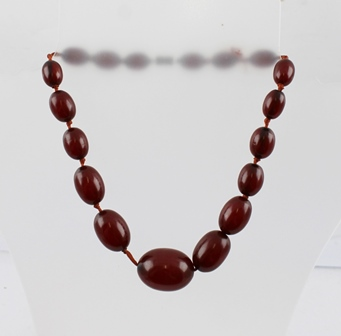 AN EARLY 20TH CENTURY GRADUATED AMBER BEAD NECKLACE of red colour, having brass screw fastener, overall length approx 43cm