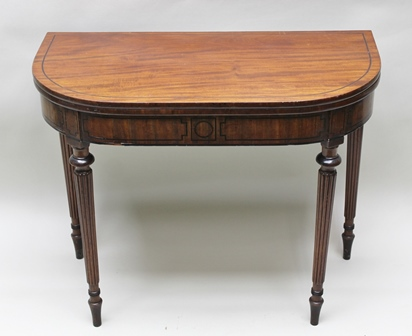 A REGENCY DESIGN MAHOGANY FOLD-OVER TEA TABLE, having string inlaid line to top and frieze, raised on turned, tapering fluted supports, 91cm wide