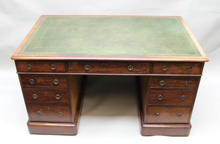 A 19TH CENTURY MAHOGANY TWIN PEDESTAL WRITING DESK having green tooled leather top, nine fitted drawers with brass ring drop handles, 138cm x 83cm