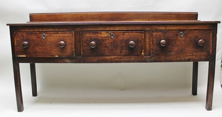 A GEORGE III OAK THREE-DRAWER DRESSER BASE, having plank gallery back, mahogany crossbanded, fitted knob handles, raised on squared supports, 184cm wide