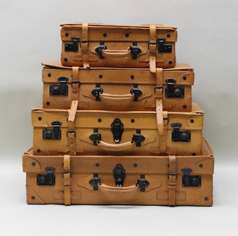 A GRADUATED SET OF FOUR GIOVANNI LEATHER SUITCASES with strap fastenings, larges 76cm wide, smallest 46cm wide