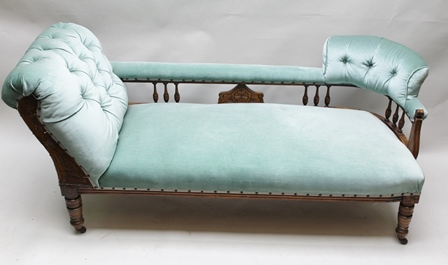 AN EDWARDIAN BEECH FRAMED CHAISE LONGUE having carved and spindle decoration, button back design with supports to either end, upholstered in a pale green dralon fabric, raised on ring turned fore feet with castors