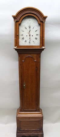 A 19TH CENTURY OAK LONGCASE CLOCK, having arch top hood flanked by columns, the arched enamel dial with Roman numerals and 8-day striking movement the trunk with arch top door, the base on bracket feet, 209cm high