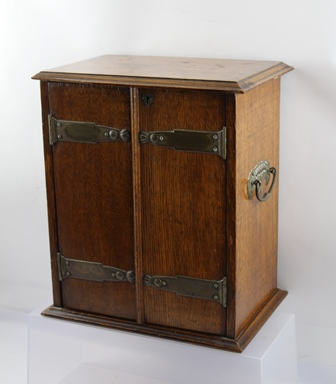 AN EDWARDIAN OAK SMOKERS CABINET with Art Nouveau design shaped metal handles and hinges, opening to reveal drainers and rotating section, 29cm wide x 34cm high, together with SMOKING RELATED CONTENTS, including a carved Meerschaum pipe, the bowl with Sultans mask